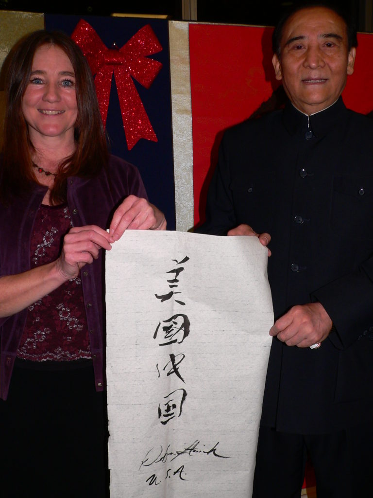 World renowned calligrapher, Guodong LI, teaches Debra Stasiak calligraphy at his United Nations 65th anniversary exhibit held in December 2013